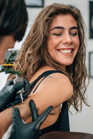 Tattoo. Pretty girl getting a tattoo. Toned image, focus on girls face.  Stock Photo