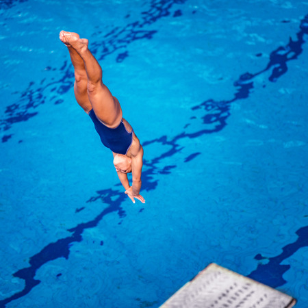 Female diver jumping into the pool from diving board 스톡 콘텐츠
