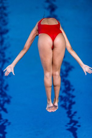 swimm: Female diver jumping into the pool from diving board Stock Photo