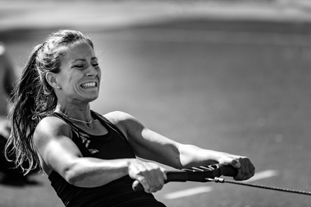 Female athlete on rowing machine on cross competition. Archivio Fotografico