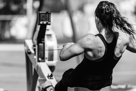 Female athlete on rowing machine on cross competition. Stock Photo