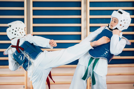 Two kids sparing on tae kwon do