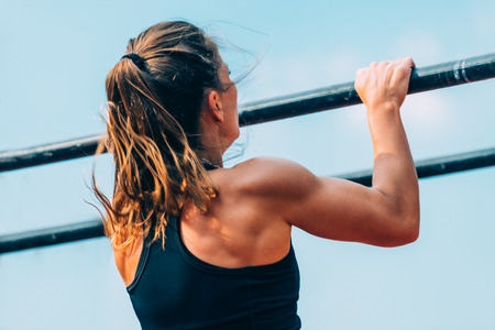 Female doing pull ups on crossfit competition Stock Photo