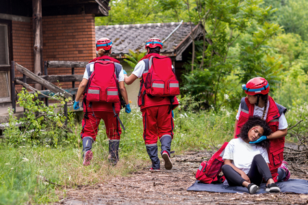 Rescue team helping injured female victim  Stock Photo