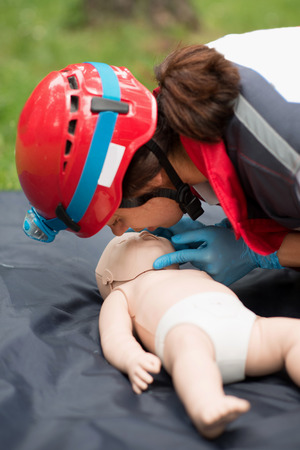 chest compression: Cpr training on baby dummy outdoors Stock Photo