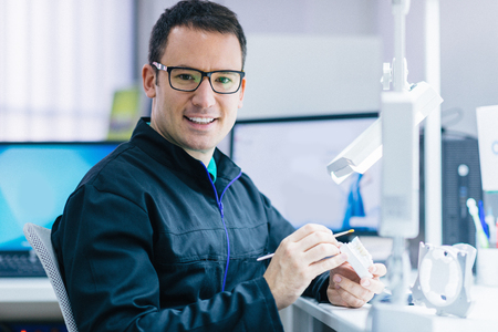 Dental technician or dentist working with tooth dentures in his laboratory