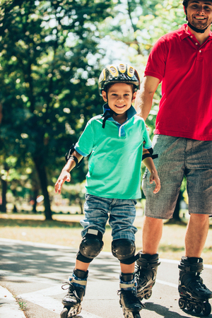 Father roller skating in park with son Stock Photo