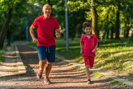 Grandfather and grandson jogging in park