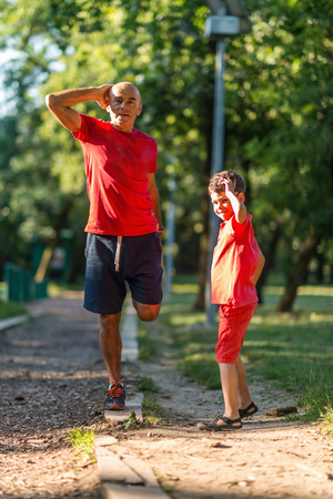 Grandfather and grandson warming up before exercising in park Stock Photo