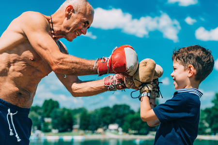Small boxer with senior trainer practicing box by the lake