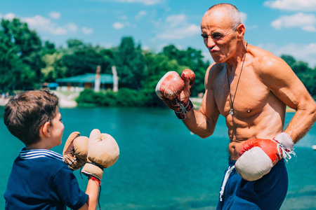 Little boy practicing boxing with grandfather by the lake