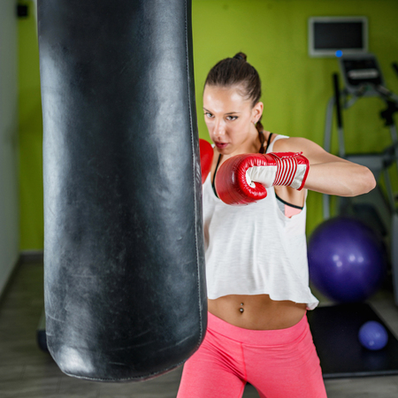 Young woman exercising in the gym on punching bag