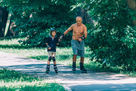 elbow pads: Grandfather and grandson enjoying roller skating in the park