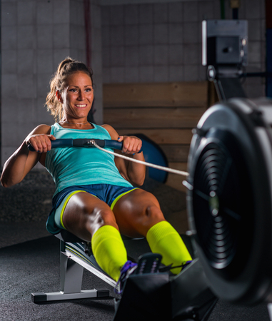 Woman athlete exercising on rowing machine Standard-Bild