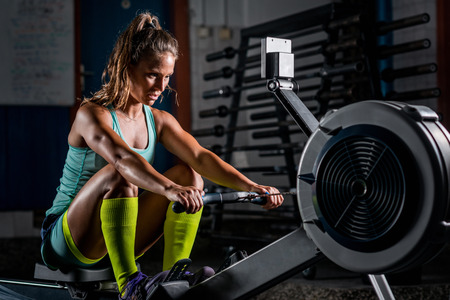 Woman athlete exercising on rowing machine 스톡 콘텐츠