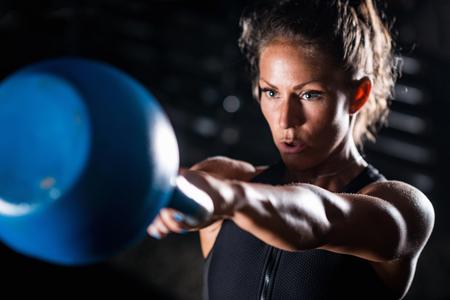 Woman athlete exercising with kettlebell indoors 版權商用圖片