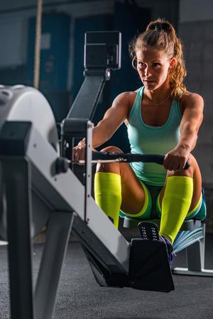 Woman athlete exercising on rowing machine 版權商用圖片