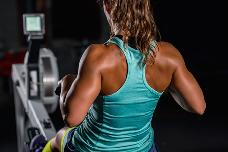 Vrouwenatleet die op het roeien van machine uitoefenen