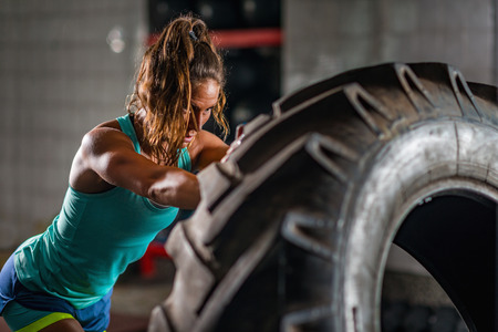 Woman athlete exercising with tire Foto de archivo