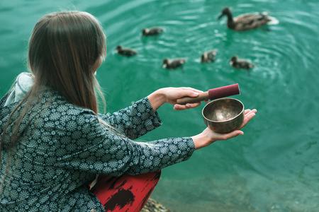 湖によるチベットの歌丼を持つ若い女性、アヒルの家族を引き付ける