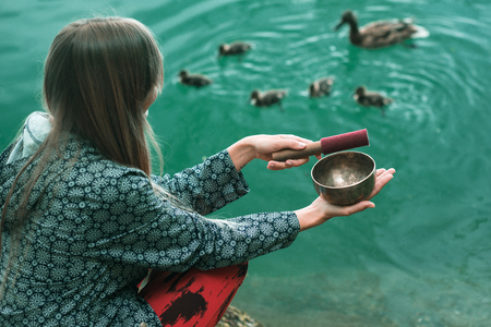 Young woman with Tibetan singing bowl by the lake, attracting duck family