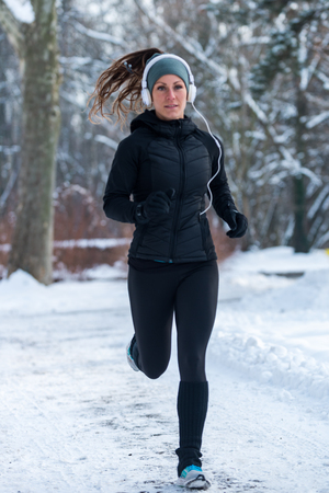 Female athlete jogging on park on winter day in park Stock Photo