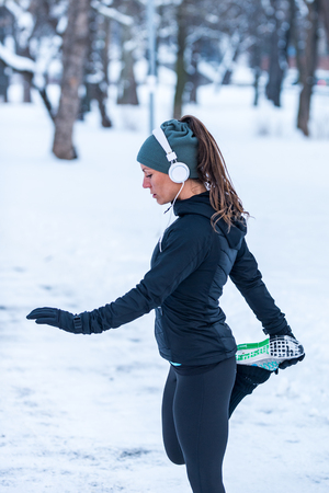 Athlète féminine exerçant dans le parc le jour de l'hiver. Écouter de la musique et faire de l'exercice Banque d'images