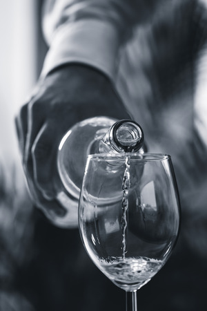 elite: Pouring white wine from bottle