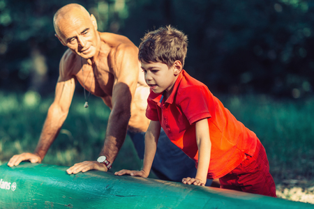 Grandfather and grandson doing pushups in park Stock Photo