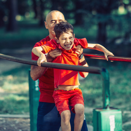 Grandfather and grandson  exercising in park Stock Photo