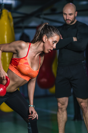 Personal trainer exercising with kettlebell with woman in the gym