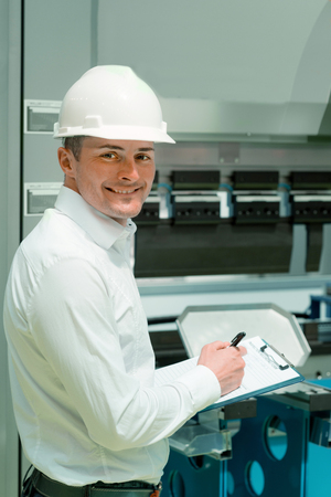 Technology Engineer Working in Factory. Holding check-list and supervising Stock Photo