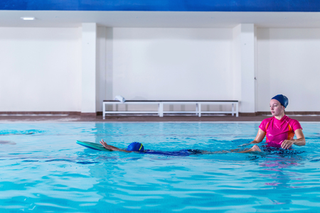 Boy having a swimming lesson with instructor 스톡 콘텐츠