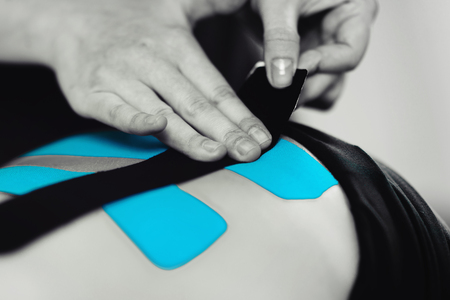Black and white image of kinesiology taping treatment with blue tape on female patient injured back. Sports injury kinesio treatment.