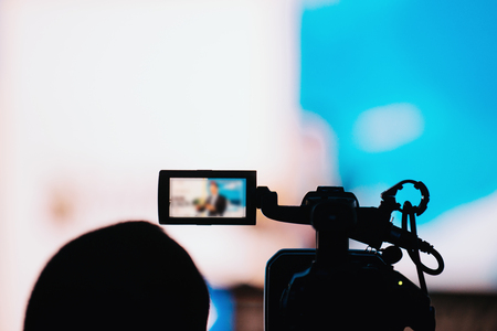 Professional digital camera silhouette recording presentation of a blurred speaker wearing suit, live streaming concept Banque d'images