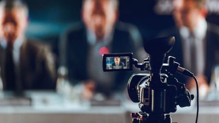 Professionele digitale camera op persconferentie, wazig sprekers pak achtergrond dragen, live streaming concept