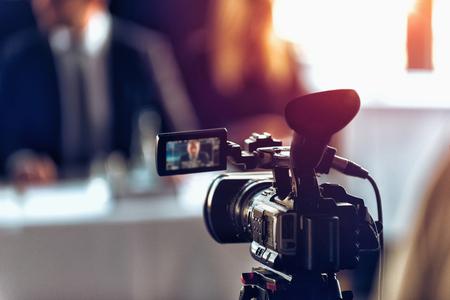 Appareil photo numérique professionnel à la conférence de presse, haut-parleurs flous portant fond de costume, concept de diffusion en direct