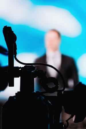 Silhouette of professional digital camera recording presentation, defocused speaker wearing suit, live streaming concept