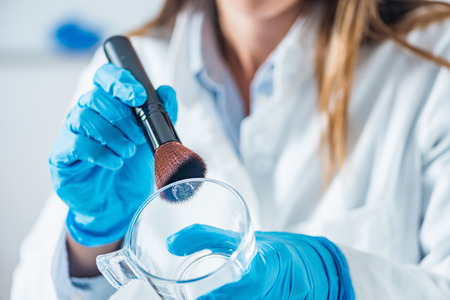Forensic scientist in a lab, looking for fingerprints Stock Photo
