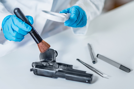 Forensic science expert examining gun collected at a crime scene Stock Photo