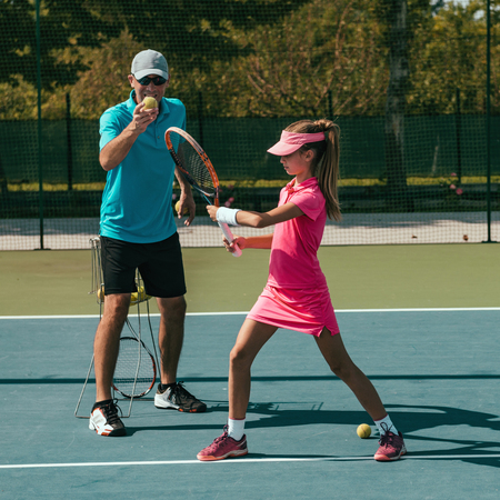 Tennis instructor with young girl on tennis training Stock Photo