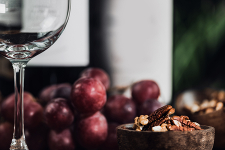 Composition with empty wine glass, different bottles of red wine, nuts in wooden bowl and fresh grapes. Close up.  写真素材