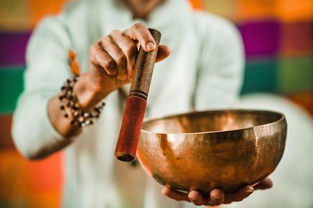 Therapist using Tibetan singing bowl in sound therapy Archivio Fotografico