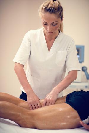 Leg massage. Female physical therapyst massaging leg of young male athelete Stock Photo