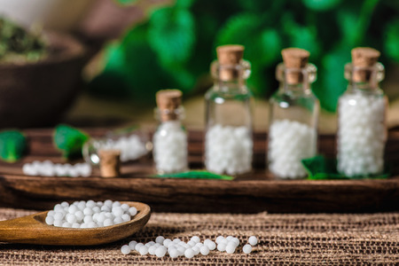 Wooden spoon and small bottles full of homeopathic globules, mint leaves in background