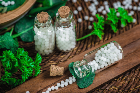 Homeopathic globules in small bottles with fresh leaves, homeopathy concept Stock Photo