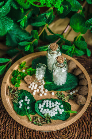 Homeopathic globules in small bottles with mint leaves in background Stock Photo
