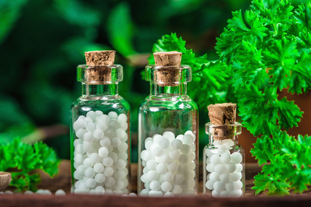 Homeopathic globules in small bottles with fresh leaves in background, homeopathy concept Foto de archivo