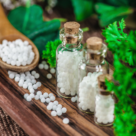 Wooden spoon full of homeopathic globules, small bottles with homeopathic pills and mint leaves in background