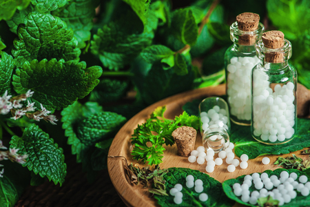 Small bottles with homeopathic pills on wooden bowl, fresh mint leaves in background